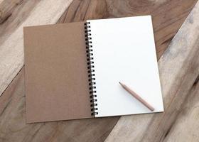 Notizbuch und Bleistift auf Holztisch foto