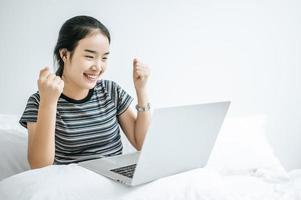 eine junge Frau spielt auf ihrem Laptop im Bett foto