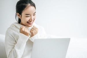 junge Frau, die ein weißes Hemd trägt, das auf ihrem Laptop spielt