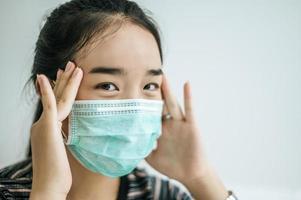 eine Frau, die ein gestreiftes Hemd und eine Schutzmaske trägt foto