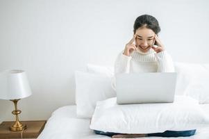 junge Frau, die ein weißes Hemd trägt, das auf ihrem Laptop spielt foto