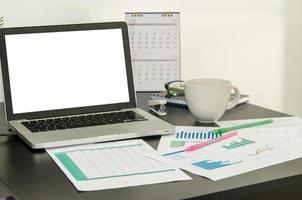 unordentlicher Schreibtisch mit Diagrammen und Kaffee