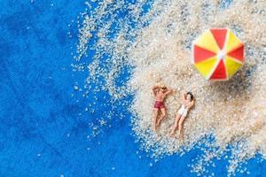 Miniaturfiguren sitzen am Strand