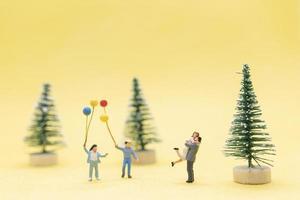 Gruppe von Figuren-Mini-Leuten, die Weihnachten feiern