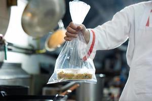 Koch hält Lebensmittelbeutel foto