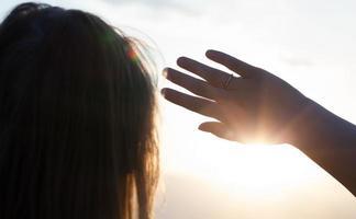 Frau, die Gesicht von der Sonne abschirmt foto