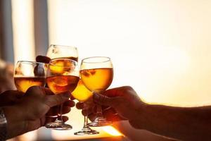 Freunde, die auf einer Party mit Wein rösten foto