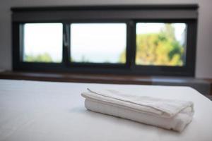 sauberes weißes Handtuch auf dem Bett im Hotelzimmer
