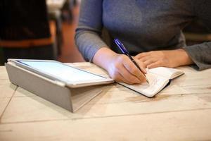 Frau, die Informationen im Notizbuch notiert