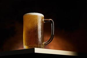 Bier im Becher auf einem Holztisch foto