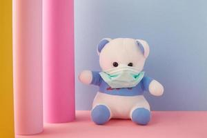 Bär, der eine Maske auf einem bunten Hintergrund trägt foto