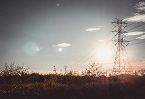 Silhouette des Hochspannungsturms mit elektrischen Drähten foto