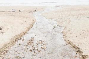 Wasser fließt vom Strand ins Meer