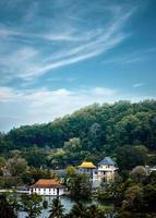 Häuser am Wasser, umgeben von Bäumen unter bewölktem blauem Himmel