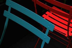 blaue und rote Metallstühle auf schwarzem Hintergrund foto
