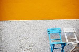 blaue und weiße Holzstühle gegen graue und orange Wand foto