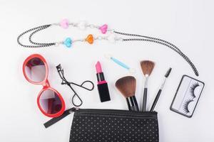 Kosmetiktasche mit Make-up-Sonnenbrille und Halskette lokalisiert auf weißem Hintergrund