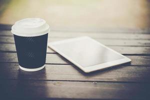 digitales Tablett auf Holztisch mit Tasse Kaffee