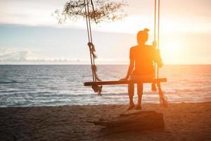 junge Frau, die den Sonnenuntergang allein auf Schaukel am Strand beobachtet