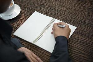 junger Mann, der auf einem Notizbuch schreibt, das an einem rustikalen Holztisch arbeitet foto