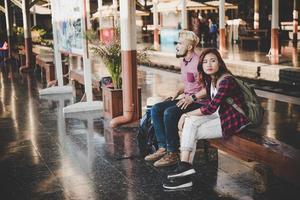junges Hipsterpaar, das auf hölzerner Bank am Bahnhof sitzt foto