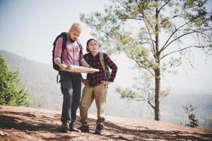 junges Touristenpaar, das zu einem Berg wandert foto