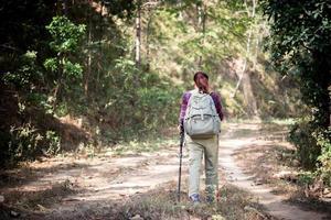 weibliche Reisende mit Rucksack auf schöner Sommerlandschaft