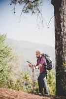 Wanderer mit Karte und großem Rucksack, der zum Berg reist