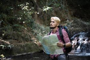 Abenteuermann, der Karte auf einem Bergweg beobachtet foto