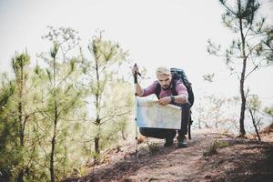 Wanderer mit Karte und großem Reiserucksack zum Berg