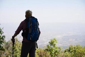 Abenteuer junger Mann, der mit einem Rucksack in den Bergen wandert foto