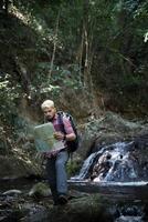 Abenteuermann, der Karte auf einem Bergweg beobachtet