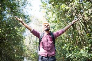 Abenteuermann, der mit einem Rucksack in den Bergen wandert foto