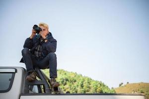 junger Fotograf sitzt auf seinem Pickup