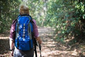 junger Mann, der in den Bergen mit einem Rucksack wandert foto