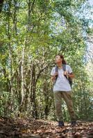 aktiver Wanderer der jungen Frau, der durch den Wald geht foto