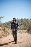 Wanderer mit Rucksack, der durch Wald spaziert und Abenteuer im Urlaub genießt foto