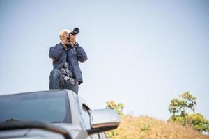 junger Fotograf, der auf seinem Kleintransporter sitzt, der einen Berg fotografiert