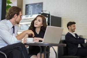 glückliche Kollegen treffen sich im Café und arbeiten am Laptop