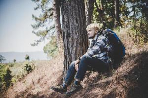 junger Mann, der mit einem Rucksack in der Natur reist