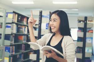 Porträt eines Studenten, der eine gute Idee in der Bibliothek hat foto