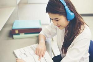 junger asiatischer Student, der in der Bibliothek liest foto