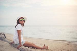 junge schöne Frau, die am Strand sitzt