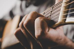 Nahaufnahme der Mannhand, die Gitarre spielt foto