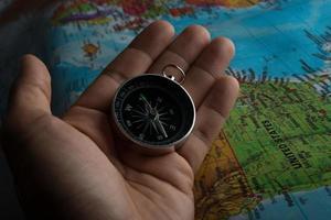 Mann hält einen Kompass auf einer Karte