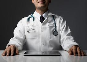 männlicher Arzt mit einem Tablet-Computer, der isoliert am Schreibtisch sitzt foto