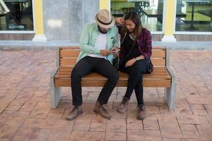 Hipster-Paar, das zusammen Musik hört, während es auf einer Bank sitzt