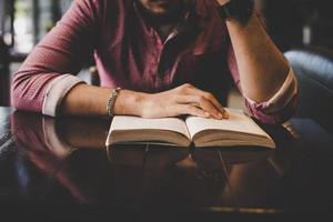 junger bärtiger Hipster, der ein Buch in einem Café liest foto