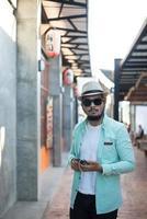Hipster-Mann, der Musik mit seinem Smartphone auf der Straße hört foto
