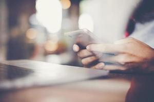 Nahaufnahme einer Frau, die mit ihrem Smartphone in einem Café arbeitet